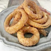 grey plate on a cutting board with crispy onion rings