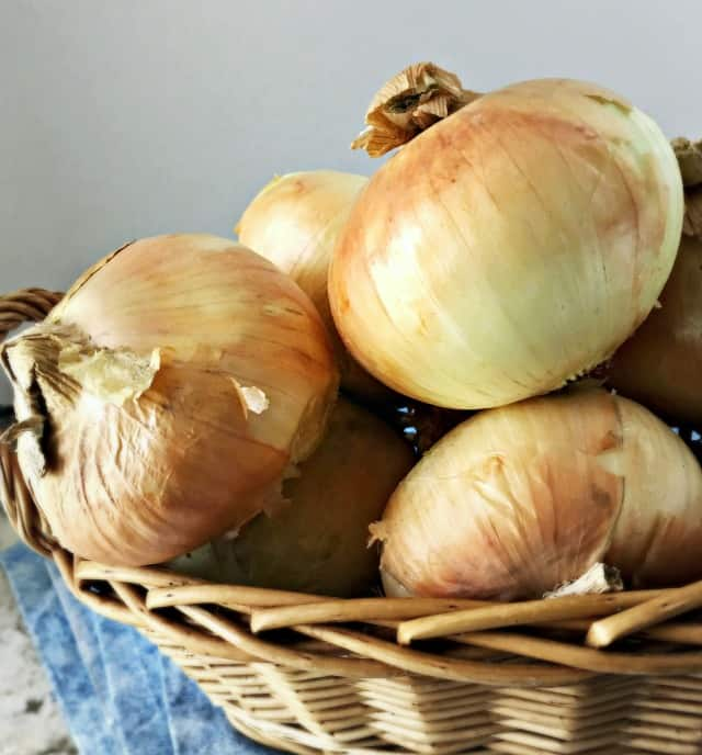 Photo of a basket of onions with blue towel for how to quarter an onion