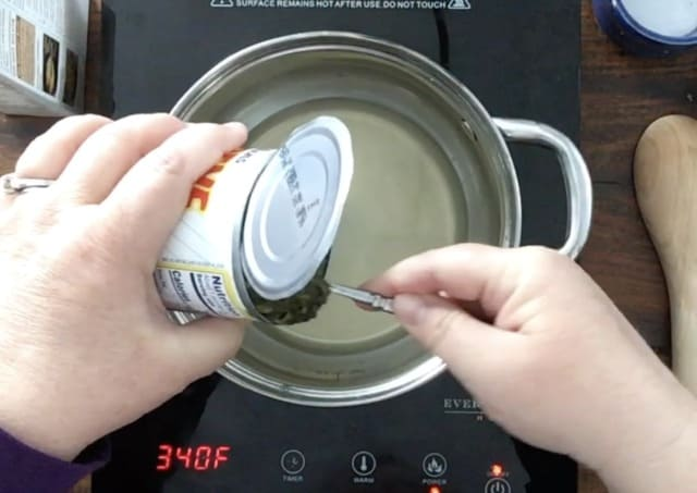 a hand scooping canned spinach into the saucepan for how to cook canned spinach