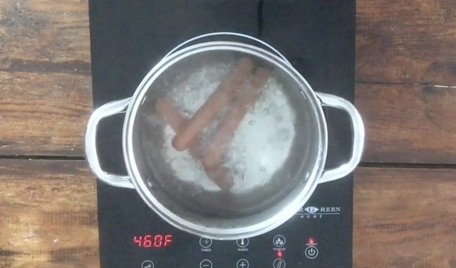 Sauce pan of full rolling boil with three submerged