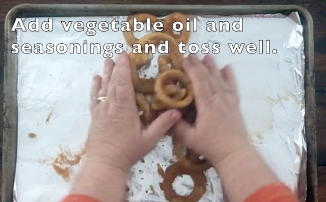 two hands tossing onion rings, oil and seasonings on a baking sheet