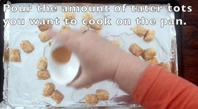 Hand adding a small bowl of seasonings for how to make frozen tater tots