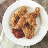 Overhead photo of three chicken strips on a white plate