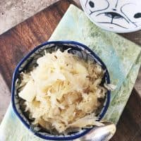 overhead shot of german sauerkraut in blue bowl, napkin, spon and extra bowl