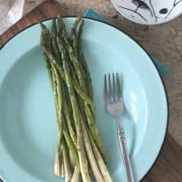 whole asparagus on blue plate with fork and butter in back ground