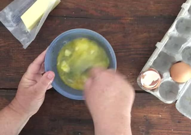 two hands mixing the eggs and other ingredients in bowl