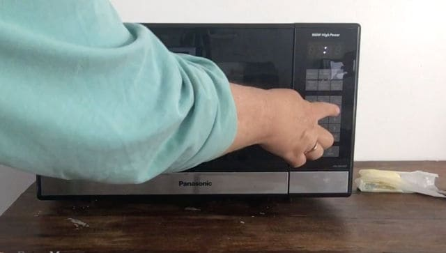 hand inputting time into a microwave panel