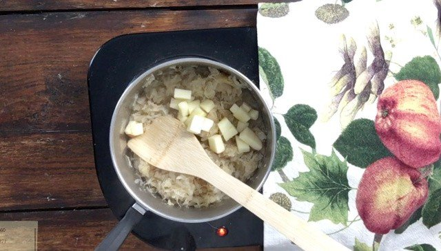 wooden spoon in saucepan for how to make canned sauerkraut