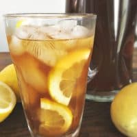 Clear glass of southern lemon iced tea with lemons floating in it.