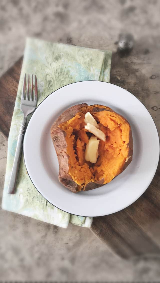 overhead photo of an orange sweet potato on a white plate with green napkin