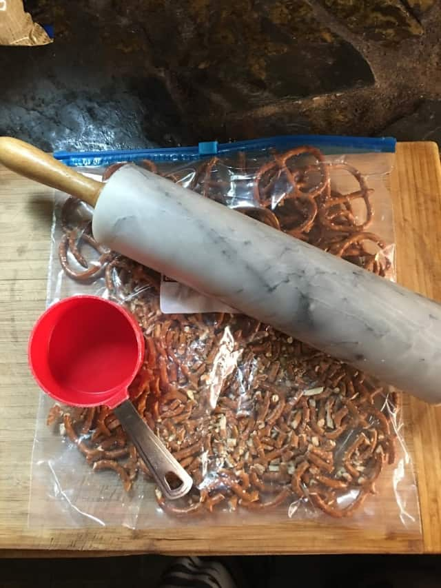 Crushed pretzels with measuring cup, rolling pin and cutting board