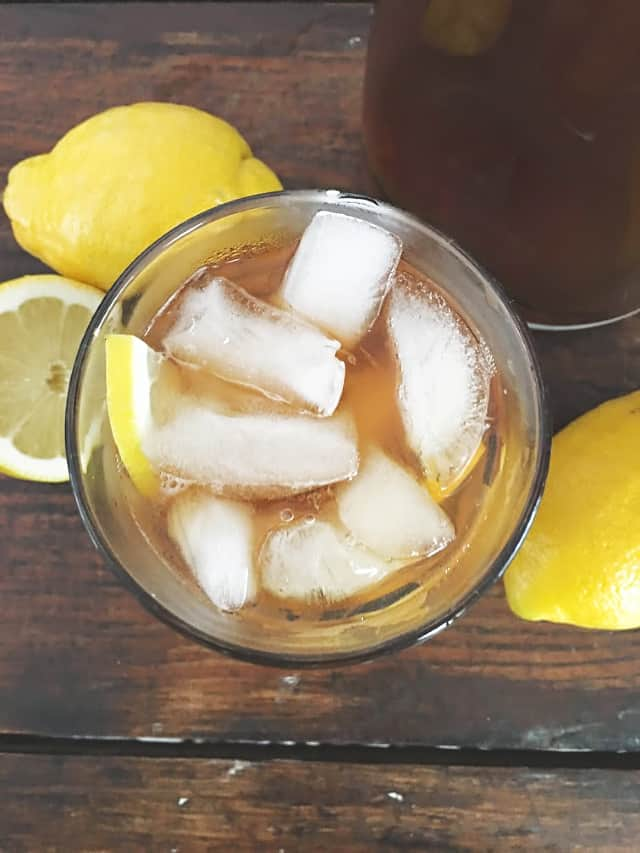 view overhead of a glass of iced tea with lemons in background