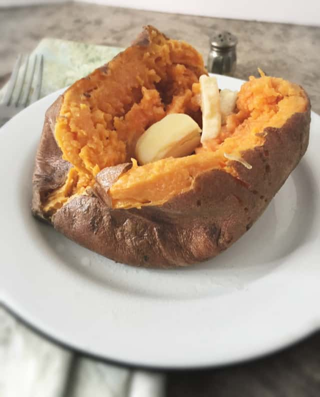side view of a sweet potato with a pat of butter on a white plate