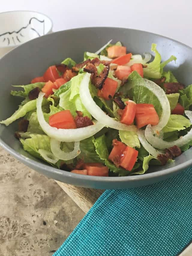 side view of gray bowl of greens, onion, tomato and bacon with dressing on brown table