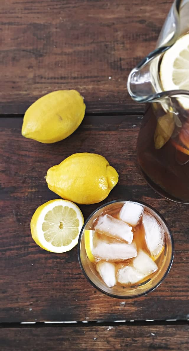 glass, pitcher and two and a half lemons on wood table