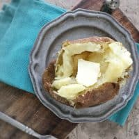 overhead photo of baked potato with butter on gray plate on blue napkin