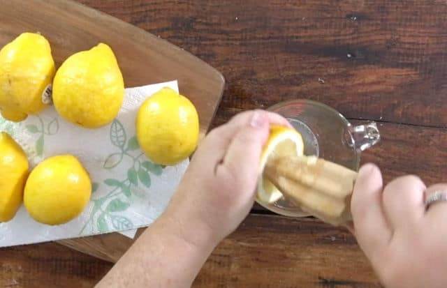 two hands using a reamer to remove juice from lemon half