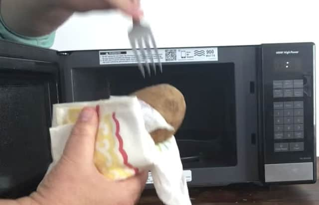 hand holding a fork while another hand holds the potato