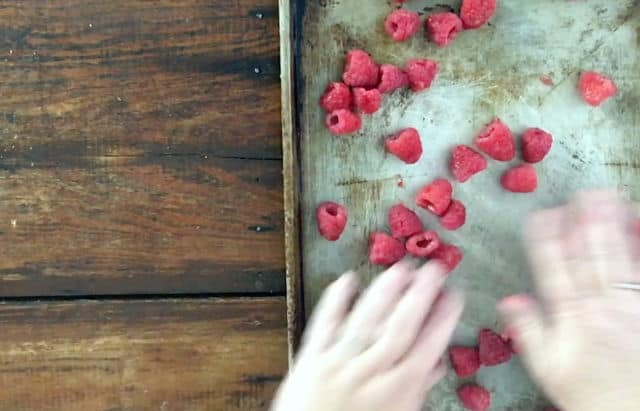 hand spreading out raspberries onto baking sheet
