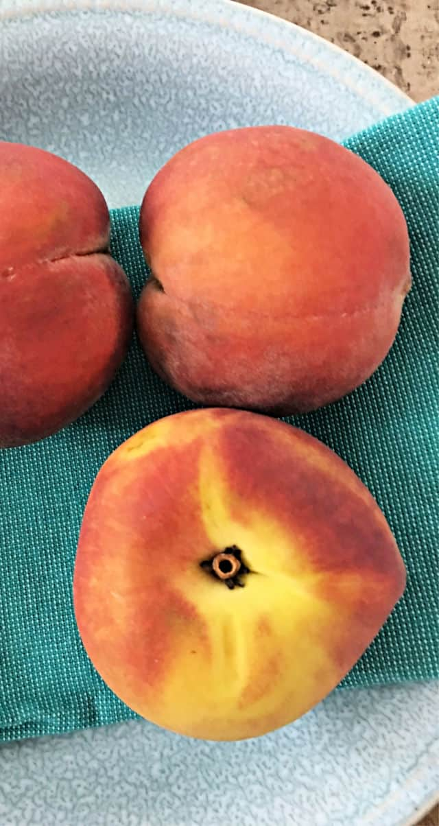 three peaches on a blue napkin in gray bowl