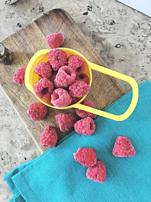 cup holding frozen raspberries on wooden background