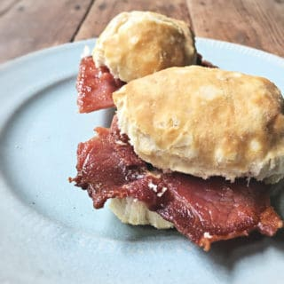 Two country ham biscuits on a blue plate on wooden table