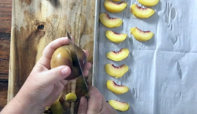 using a paring knife to cut a peach in half, peach slices on the side