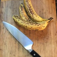 bananas on cutting board with a knife