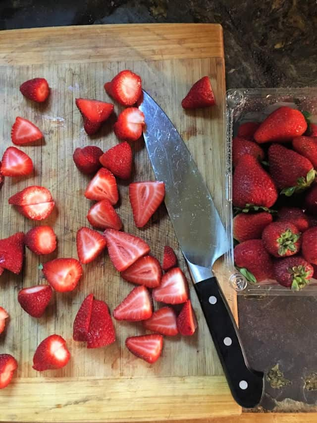 cutting board with knife and strawberries