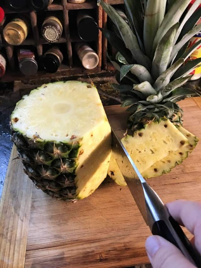 A knife cutting down the side of a pineapple