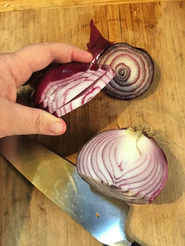 hand holding onion cut at side into slabs