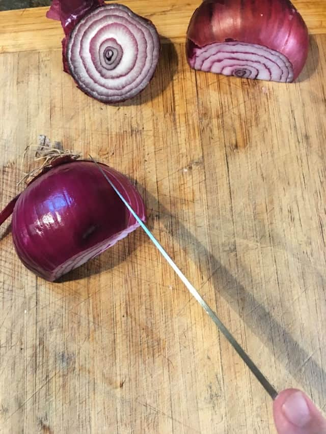Knife and onion on cutting board