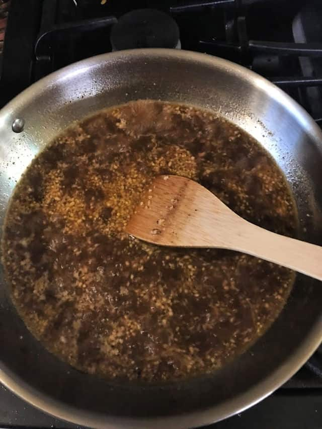 heating the sauce ingredients in pan with wooden spoon