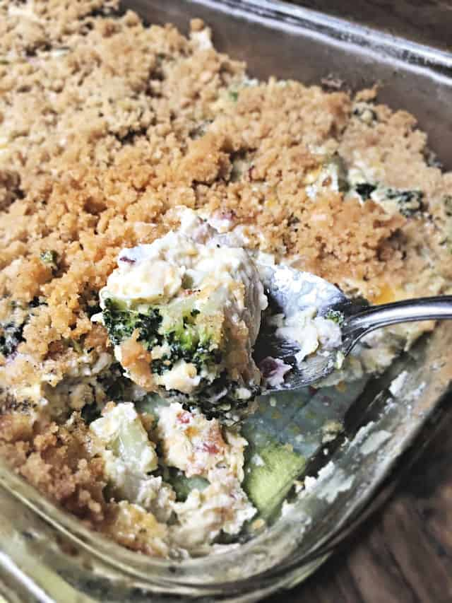 a tablespoon holding up a bite of broccoli casserole