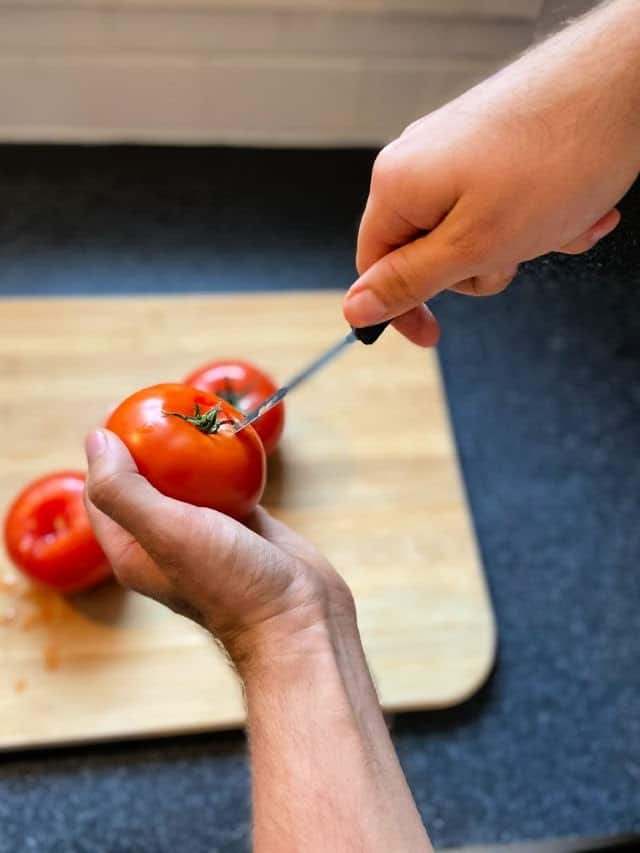 hand holding tomato and another hand poking a paring knife next to the stem