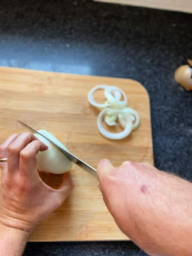 hand holding onion and the other cutting it into rings