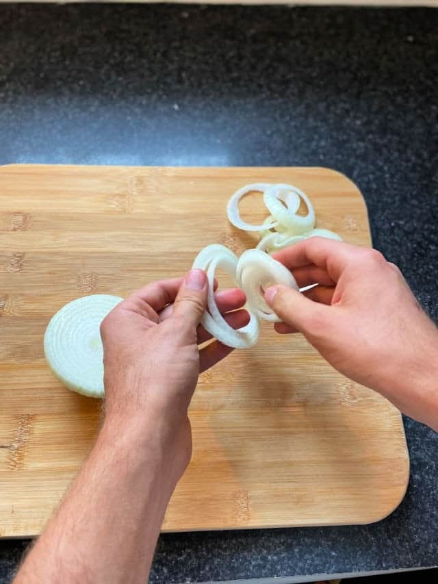 two hands separating the onion into rings
