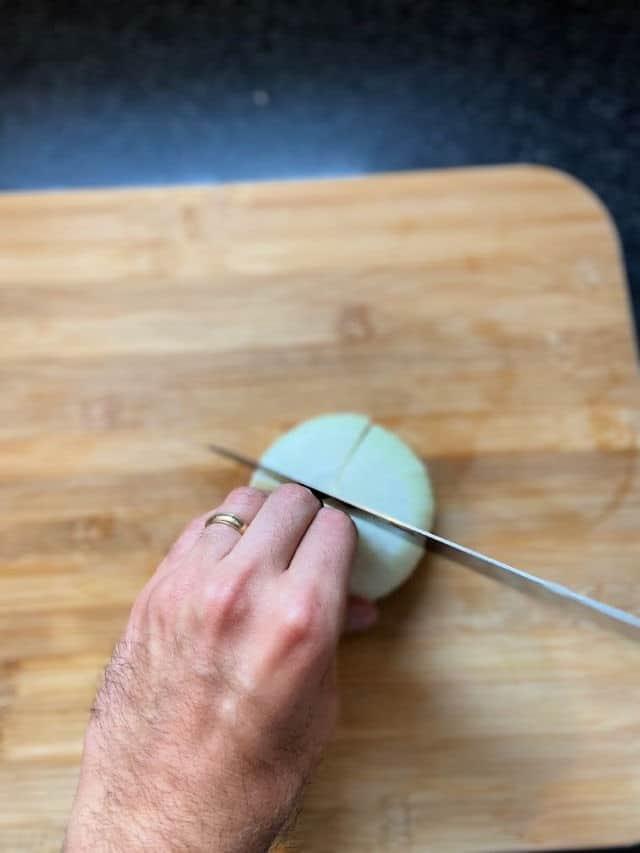 hand holding onion still on cutting board