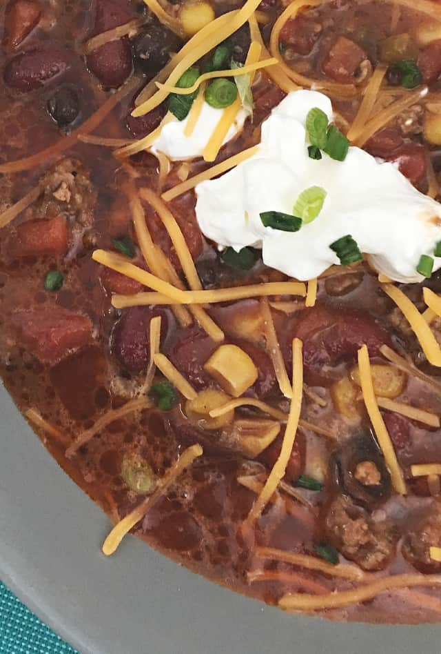 dollop of sour cream on top of close up of 8 can taco soup
