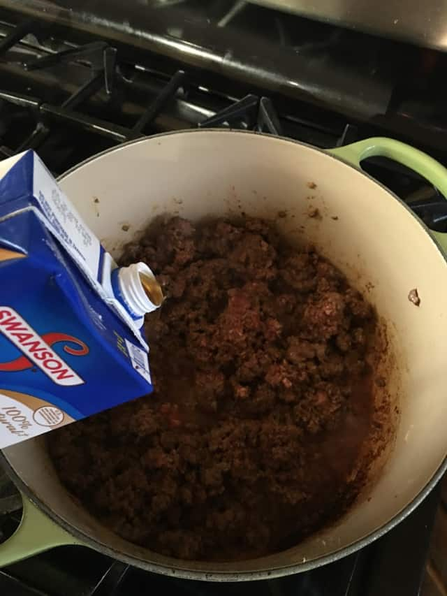 adding stock or broth to ground beef in stock pot