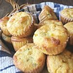 close up of mexican corn muffins in a basket with blue and white towel