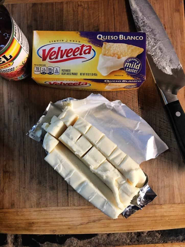 box of velveeta queso blanco, knife, rotel can, block of cheese cut into cubes