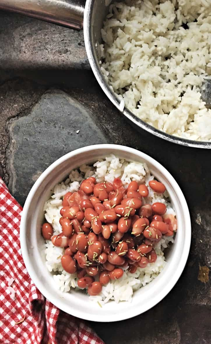 small white bowl of beans and rice with gingham towel