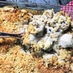 wooden spoon dipping out some easy chicken and rice casserole from glass pan