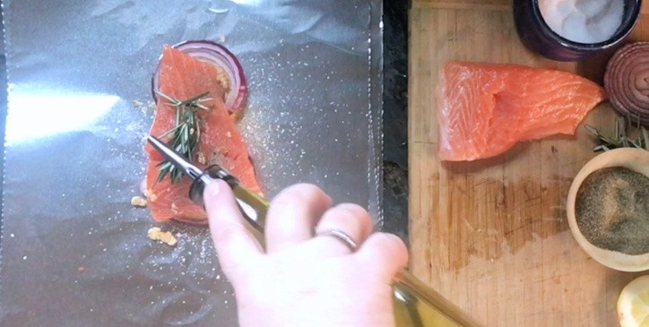 piece of salmon with hand pouring oil on top