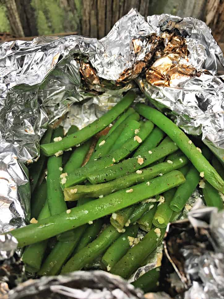 foil package opened to reveal green beans with garlic