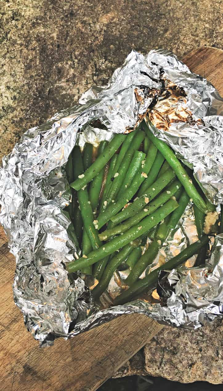 overhead shot of green beans in foil packet with scorch marks on foil