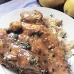 close up of lemon chicken piccata on small white plate with rice