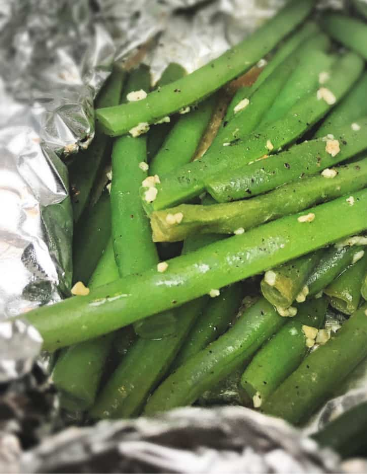 fresh green beans roasted in aluminum foil on the grill