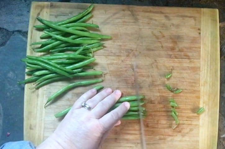 hand cutting the ends off of green beans on cutting board
